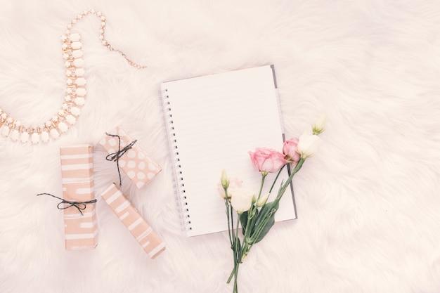 Cahier avec des roses et des coffrets cadeaux sur une couverture Photo gratuit