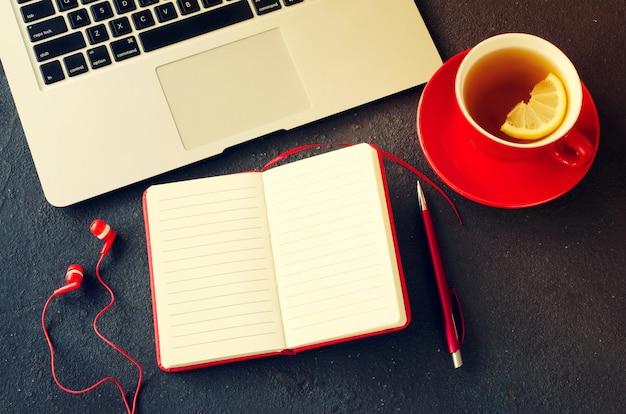 Cahier rouge vierge, ordinateur portable, casque et tasse de thé. Photo Premium