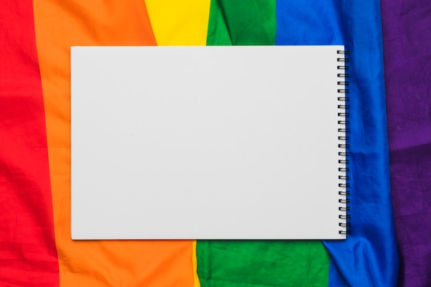 Cahier à spirale blanc sur drapeau arc-en-ciel Photo gratuit