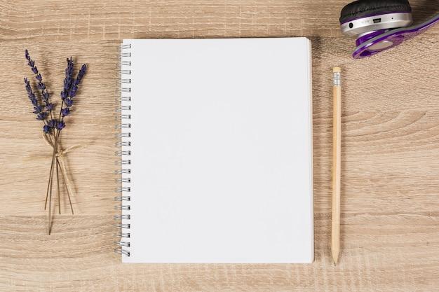 Cahier à spirale vierge; crayon; écouteurs et brindilles de lavande sur fond en bois Photo gratuit
