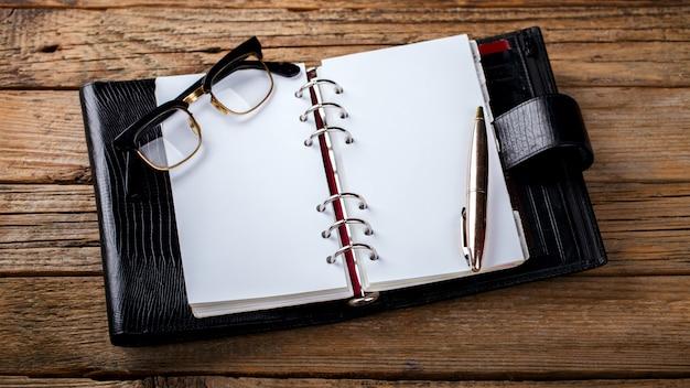 Cahier avec stylo et lunettes Photo Premium