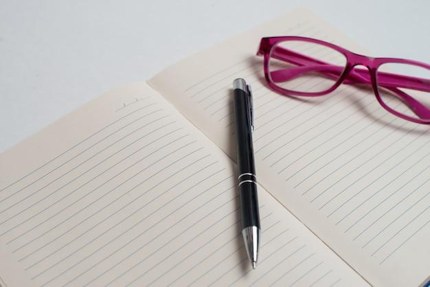 Cahier avec stylo noir et lunettes violettes Photo Premium
