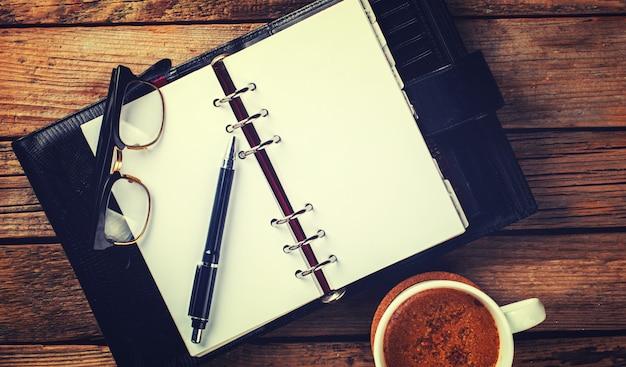 Cahier avec stylo, verres et café Photo Premium