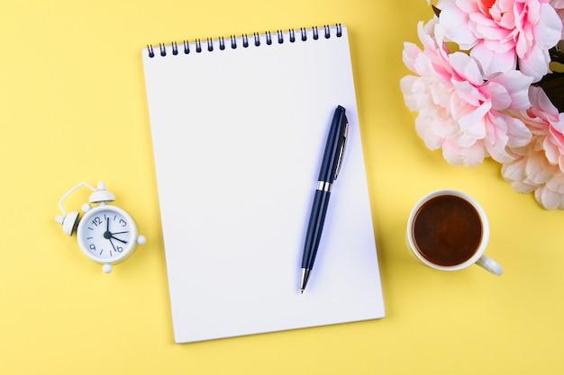 Cahier vide avec un stylo bleu sur un fond jaune pastel. maquette, cadre, gabarit. Photo Premium
