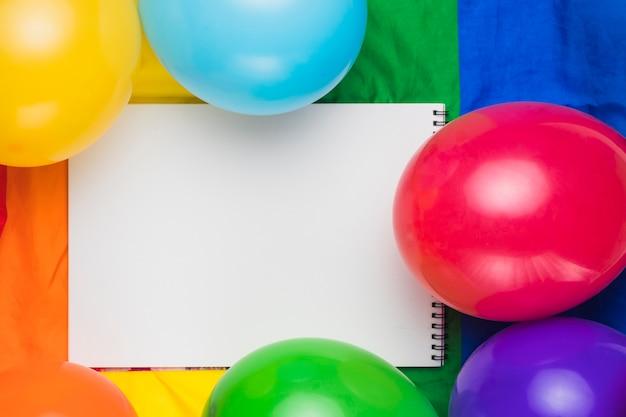 Cahier vierge et ballons colorés Photo gratuit