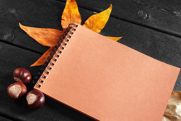 Cahier vierge entouré de feuilles d'automne Photo Premium