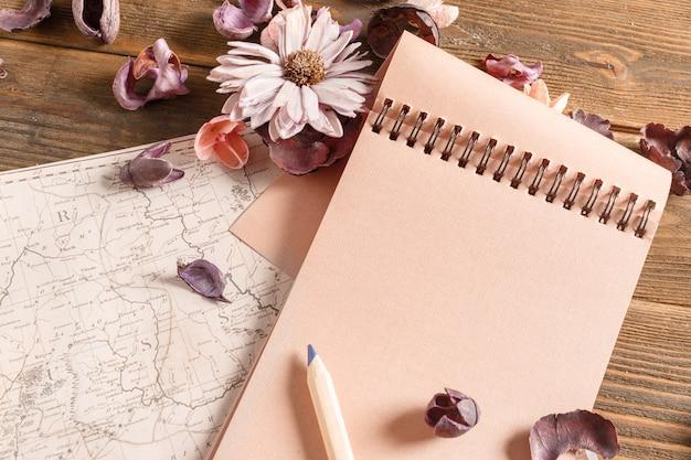 Cahier vierge avec fleur sur table en bois vintage Photo Premium
