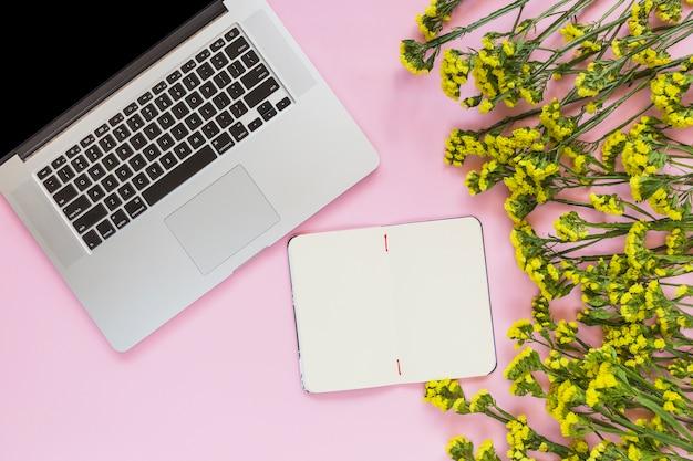 Cahier vierge; fleurs jaunes et ordinateur portable sur fond rose Photo gratuit