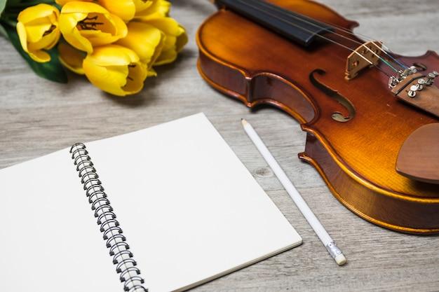 Un cahier vierge ouvert crayon; tulipe et violon classique sur fond de planche Photo gratuit