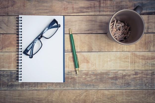 Cahier vierge avec stylo et lunettes sur fond de bois Photo Premium