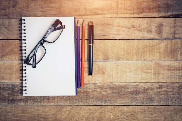 Cahier vierge avec stylo et lunettes sur table en bois Photo Premium