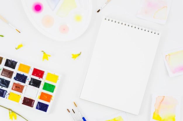 Cahier vue de dessus avec aquarelle et pétales Photo gratuit