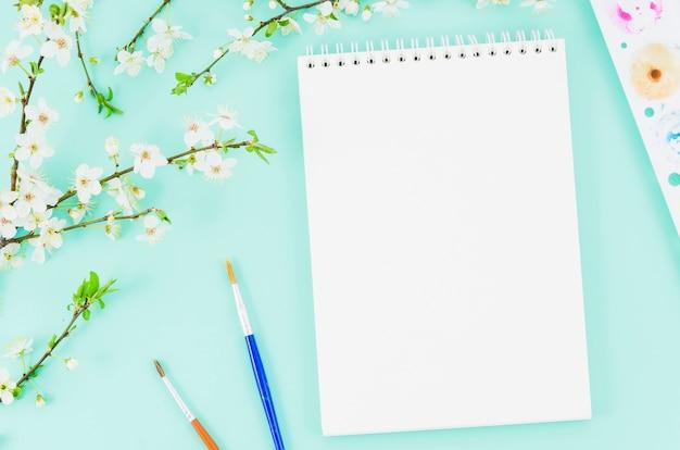 Cahier vue de dessus avec branche de fleur Photo gratuit