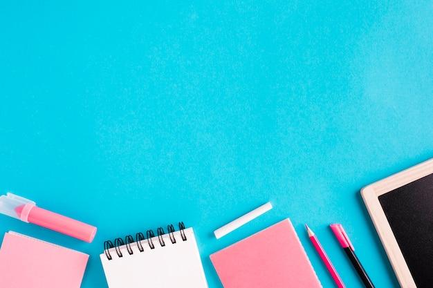 Cahiers et papeterie sur fond coloré Photo gratuit