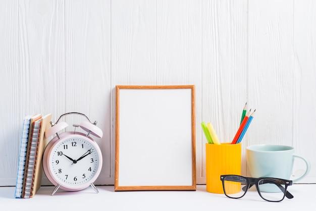 Des cahiers; réveil; cadre vierge; porte-crayons; tasse et lunettes contre papier peint en bois blanc Photo gratuit