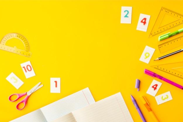 Cahiers, stylos, crayons, chiffres et règles sur fond jaune Photo Premium