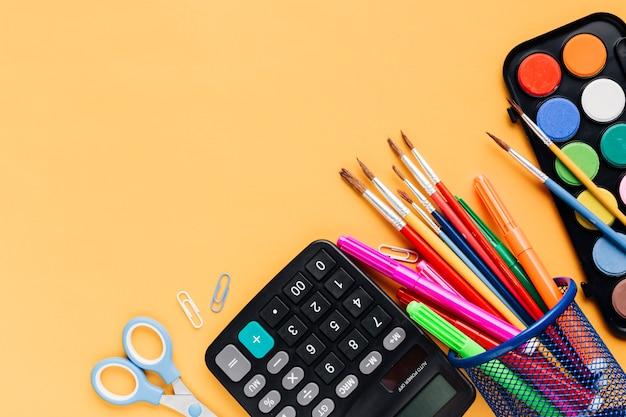 Calculatrice avec des ciseaux et des outils de dessin dispersés sur un bureau jaune Photo gratuit
