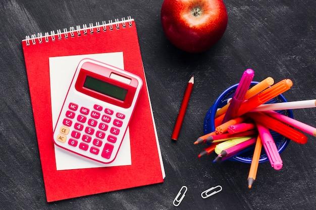 Calculatrice à côté de crayons lumineux Photo gratuit