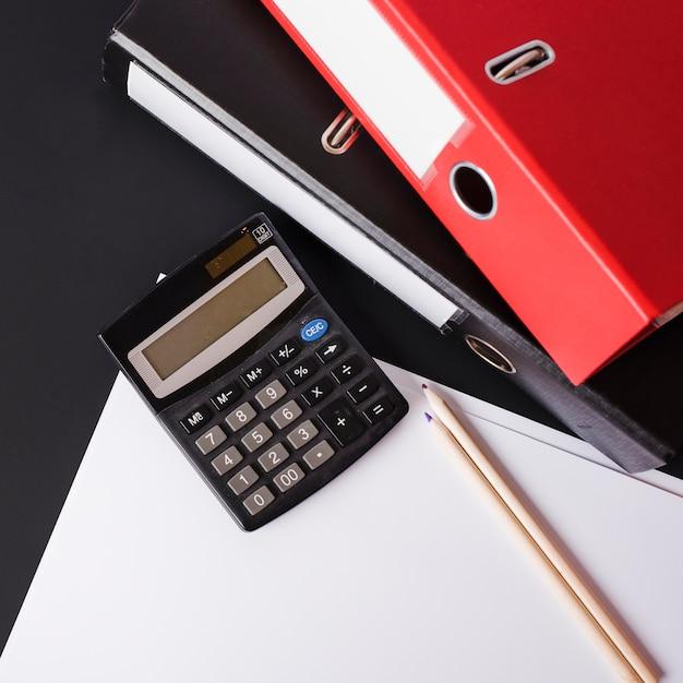 Calculatrice; des crayons; papiers et fichiers papier sur fond noir Photo gratuit