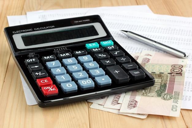 Calculatrice électronique, stylo en métal et argent russe sur des feuilles de papier avec des chiffres. Photo Premium