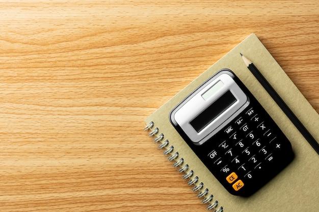 Calculatrice et fournitures de bureau sur une table en bois. - vue de dessus avec espace de copie. Photo Premium