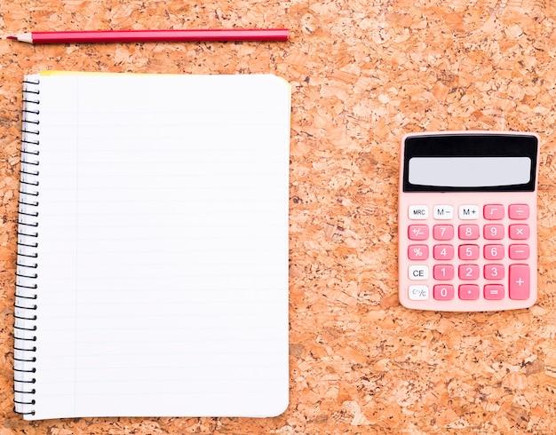 Calculatrice près de cahier et un crayon Photo gratuit