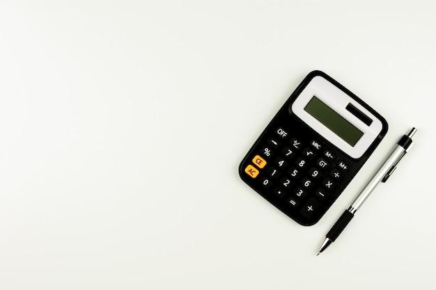 Calculatrice et et un stylo sur la table blanche Photo Premium