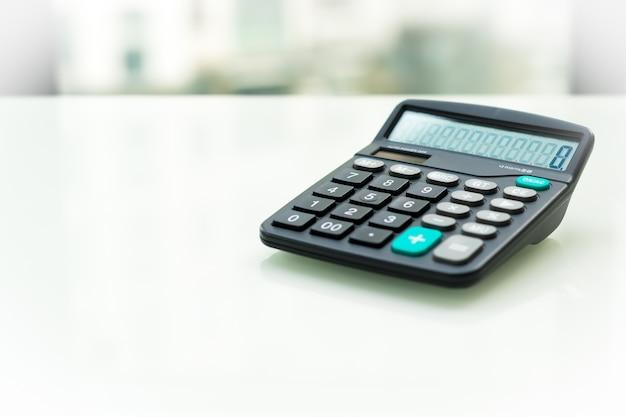 Calculatrice sur la table blanche près de la fenêtre Photo Premium