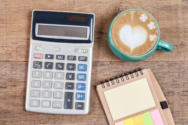 Calculatrice et tasse de café sur table en bois. Photo Premium