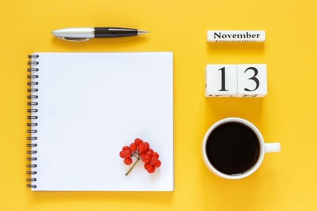 Calendrier 13 novembre tasse de café, bloc-notes avec stylo et feuille jaune sur jaune Photo Premium