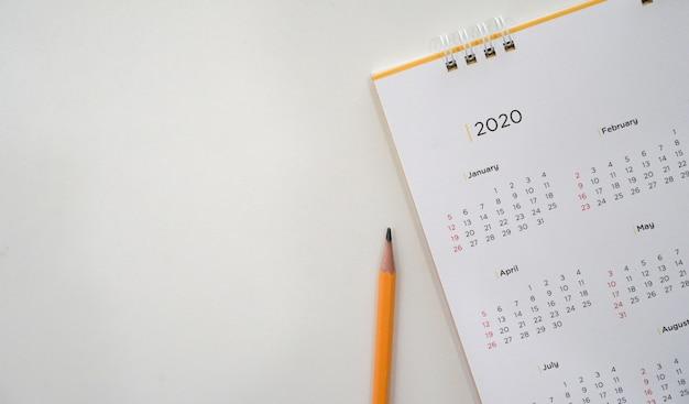 Calendrier 2020 avec un crayon jaune et calendrier mensuel pour prendre rendez-vous Photo Premium