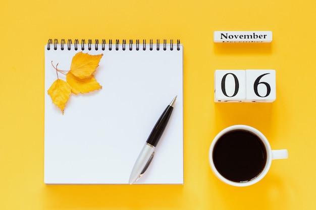 Calendrier 6 novembre tasse de café, bloc-notes avec stylo et feuille jaune sur une surface jaune Photo Premium