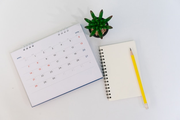 Calendrier avril 2019 avec carnet, stylo et plante au bureau avec concept de vue de dessus Photo Premium