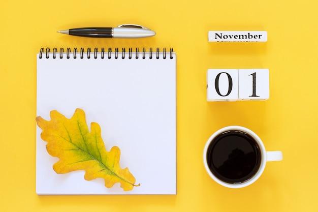 Calendrier bois 1 tasse de café, bloc-notes avec un stylo et une feuille jaune sur fond jaune Photo Premium
