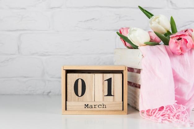 Calendrier en bois avec le 1er mars près de la caisse en bois avec des tulipes et une écharpe sur un bureau blanc Photo gratuit
