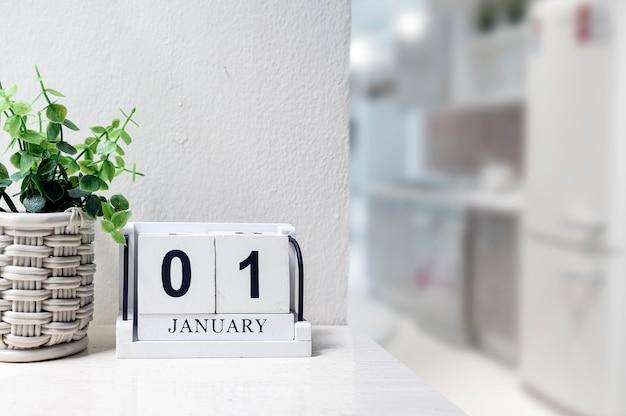 Calendrier en bois blanc avec mot noir du 1er janvier sur la table dans la salle blanche Photo Premium