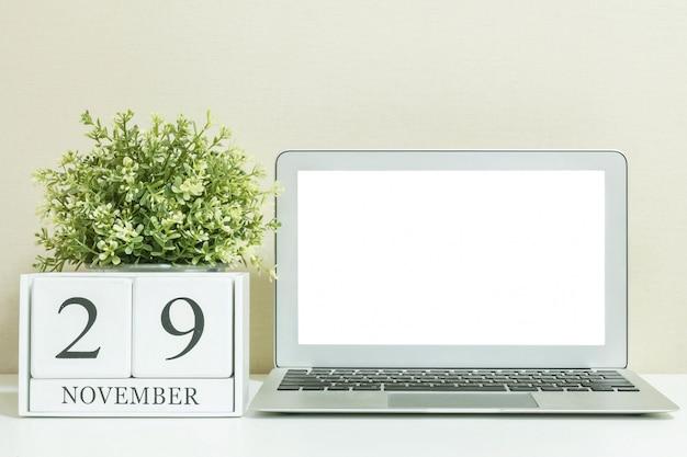 Calendrier en bois blanc avec mot noir du 29 novembre avec ordinateur portable Photo Premium