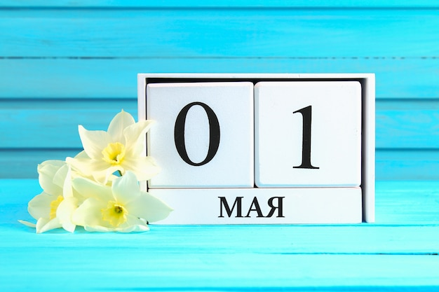 Calendrier en bois blanc avec le texte en russe: 1er mai. fête du travail et printemps. Photo Premium