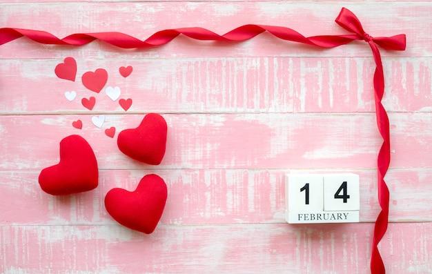 Le calendrier en bois du 14 février est composé d'un ruban rouge et d'un cœur Photo Premium