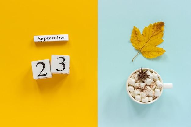 Calendrier en bois du 23 septembre, tasse de cacao avec des guimauves et des feuilles d'automne jaunes sur fond bleu jaune. Photo Premium