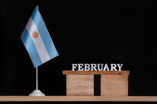 Calendrier En Bois De Février Avec Drapeau Argentin Sur Fond Noir. Vacances De L'argentine En Février. Photo Premium