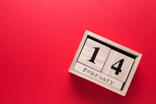 Calendrier En Bois Avec L'inscription Du 14 Février Sur Un Fond Isolé Rouge. Photo Premium