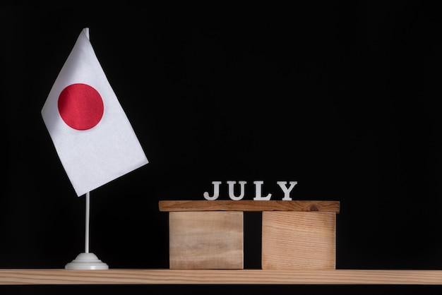 Calendrier En Bois De Juillet Avec Le Drapeau Du Japon Sur Fond Noir. Photo Premium