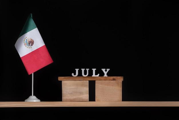 Calendrier En Bois De Juillet Avec Le Drapeau Du Mexique Sur Fond Noir. Photo Premium