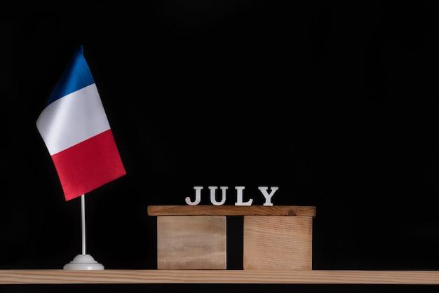 Calendrier En Bois De Juillet Avec Drapeau Français Sur Fond Noir. Vacances De France En Juillet. Photo Premium