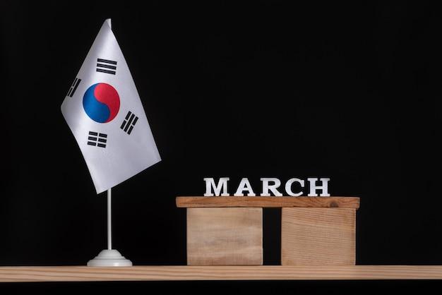 Calendrier En Bois De Mars Avec Drapeau De La Corée Du Sud, Fond Noir. Jours Fériés De La Corée Du Sud En Mars. Photo Premium