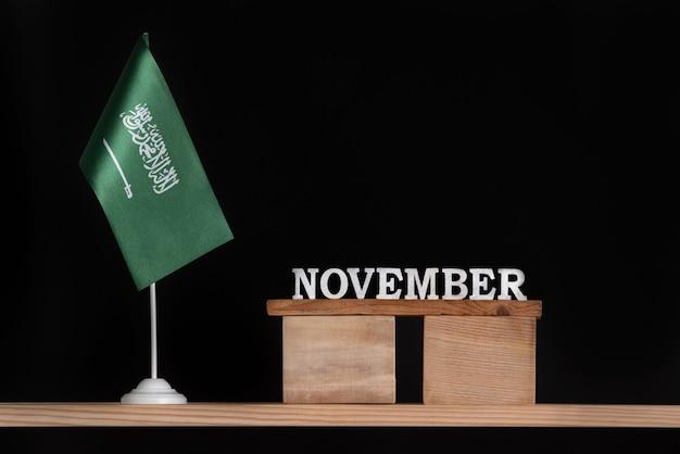 Calendrier En Bois De Novembre Avec Le Drapeau De L'arabie Saoudite Sur Fond Noir. Dates De L'arabie Saoudite En Novembre. Photo Premium