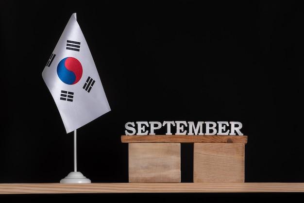 Calendrier En Bois De Septembre Avec Le Drapeau De La Corée Du Sud Sur Fond Noir. Dates De La Corée Du Sud En Septembre. Photo Premium