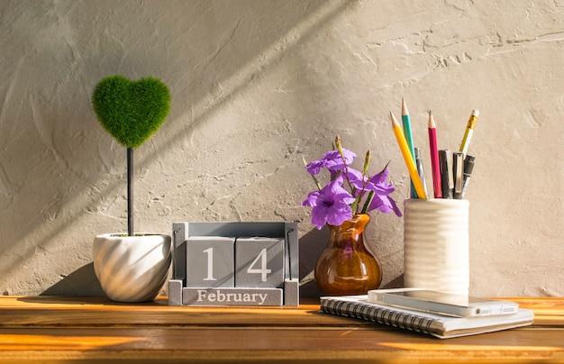Calendrier en bois vintage pour le 14 février avec coeur vert sur fond de concept de l'amour de la table en bois et saint valentin, toile de fond. Photo Premium