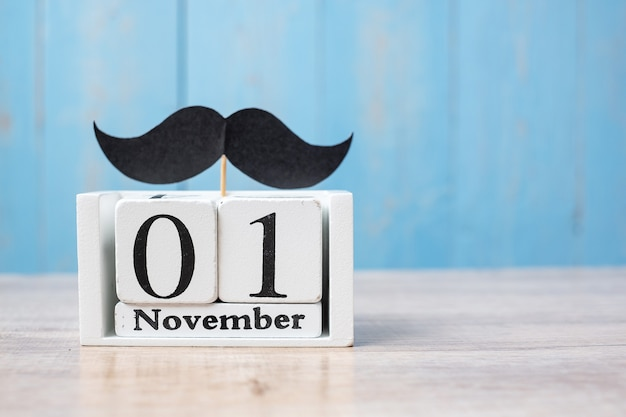 Calendrier du 1er novembre et moustache sur table en bois. père, journée internationale des hommes, sensibilisation au cancer de la prostate Photo Premium